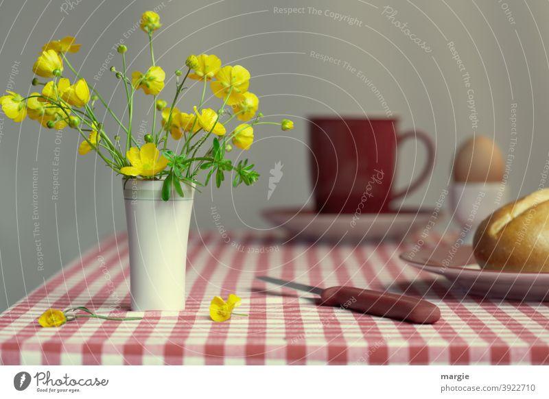 Eine Vase mit Butterblumen steht auf einem Frühstückstisch mit rotkarierter Tischdecke. Ein Brötchen auf einem Teller mit einem Messer, im Hintergrund eine rote Tasse auf einem Unterteller und ein gekochtes Ei in einem Eierbecher