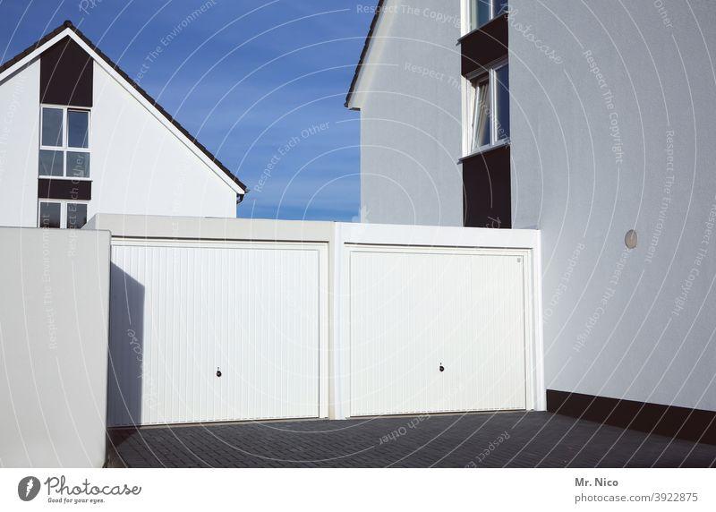 Doppelgarage Garage Architektur Gebäude Haus Garagentor Fassade Einfahrt geschlossen weiß Fenster spießig Neubaugebiet Blauer Himmel Schatten Stadtrand