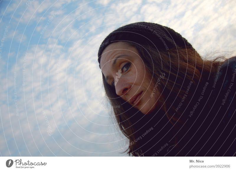 Mimik blick portrait Frau Porträt Blick in die Kamera schön feminin Gesicht langhaarig natürlich Mütze Himmel Wolken frech frech in die kamera grinsen