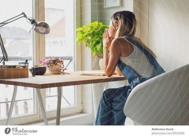 Nachdenkliche Frau sitzt am Tisch zu Hause nachdenklich besinnlich nachdenken sich auf die Hand lehnen heimwärts Denken Windstille einsam Vorstellungskraft