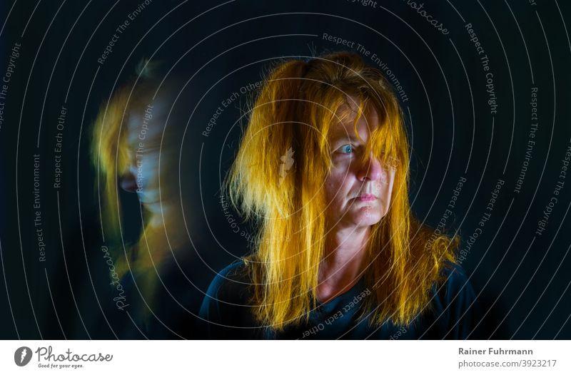 Eine Frau mit roten Haaren steht in der Dunkelheit. Sie blickt panisch in ein Licht. Porträt Panik schwarz Blick Schatten Angst Gesicht dunkel Nacht bedrohlich