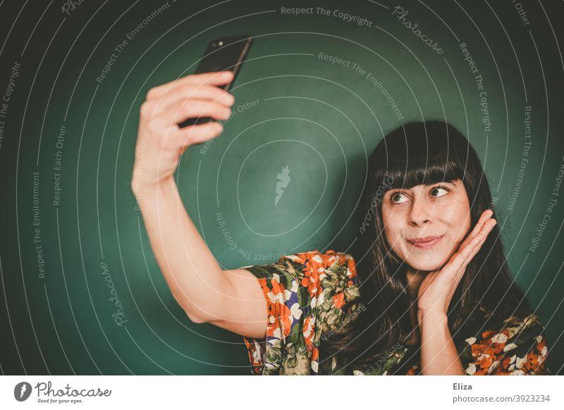 Junge Frau macht ein Selfie mit ihrem Smartphone junge Frau Eitelkeit selbstverliebt Selbstportrait Influencerin Handy Telefon Gesicht brünett braunhaarig