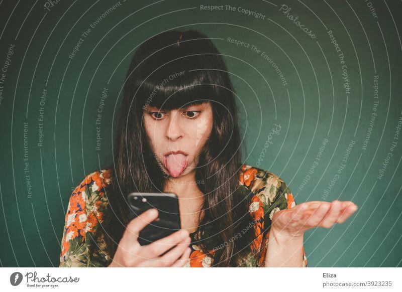 Junge Frau streckt ihrem Handy genervt die Zunge raus Smartphone frustriert ungeduldig rausstrecken Gesicht Zunge rausstrecken frech Online Dating lustig