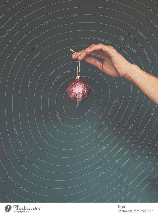 Frohe Weihnachten   Hand hält Christbaumkugel Baumschmuck weihnachtlich elegant Glitzer rosa Weihnachtsbaumkugel golden Weihnachtsdekoration