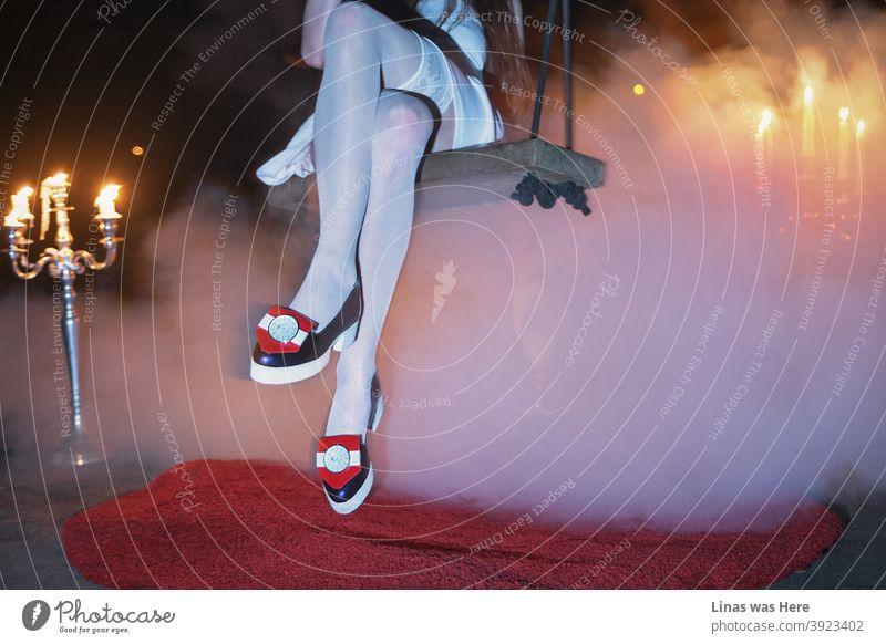 Modisches Mädchen mit avantgardistischen Schuhen schwingt unter der Brücke. Rauch mit Kronleuchtern schafft eine mystische Atmosphäre. Dies ist kein typisches Mode-Fotoshooting.