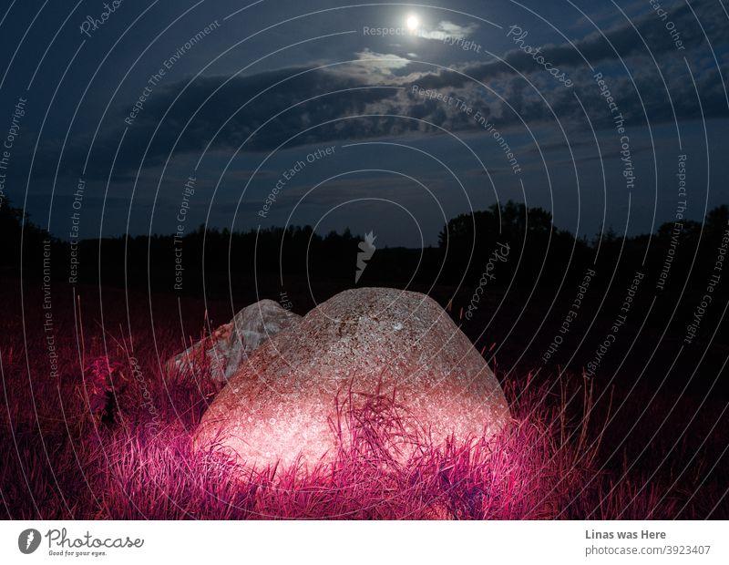 Violettes Licht leuchtet in dieser Sommernacht auf einen riesigen Stein. Mysteriöse Beleuchtung mitten in der Nacht und der Vollmond macht es nur noch gespenstischer.