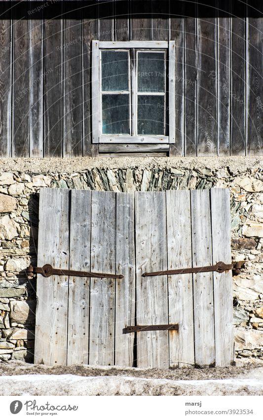 Zeitgeschichte | Früher war alles Besser. Fassade einer alten Scheune, mit zweiflügeligem Holztor und einem Fenster im oberen Bereich. Steinmauer Mauer Torbogen