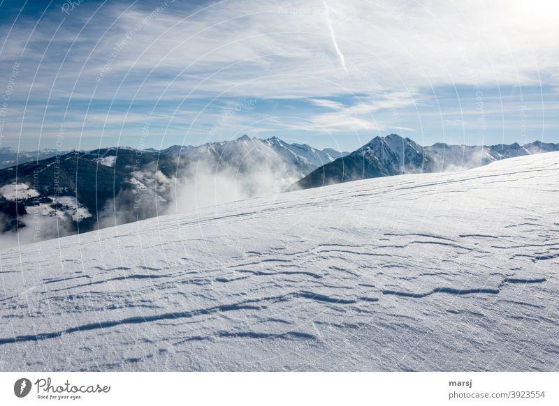Windgeformte Schneedecke mit der Planai und mehreren Berggipfeln im Hintergrund Schneebedeckte Gipfel bewölkt Himmel Landschaft Schönes Wetter Alpen