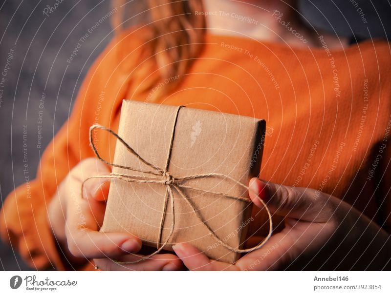Junge Frau hält eine Kraft-Geschenk-Box, eingewickelt in einfachen braunen Papier, Valentinstag, Geburtstag, Mothers Day Geschenk oder Geschenk-Konzept selektiven Fokus, dunklen Hintergrund