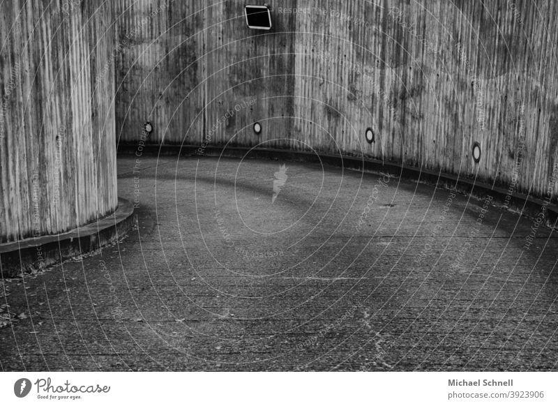 Einfahrt in ein unterirdisches Parkhaus Parkhauseinfahrt Kurve kurvig links links herum grau grau in grau Menschenleer Außenaufnahme Beton Textfreiraum unten