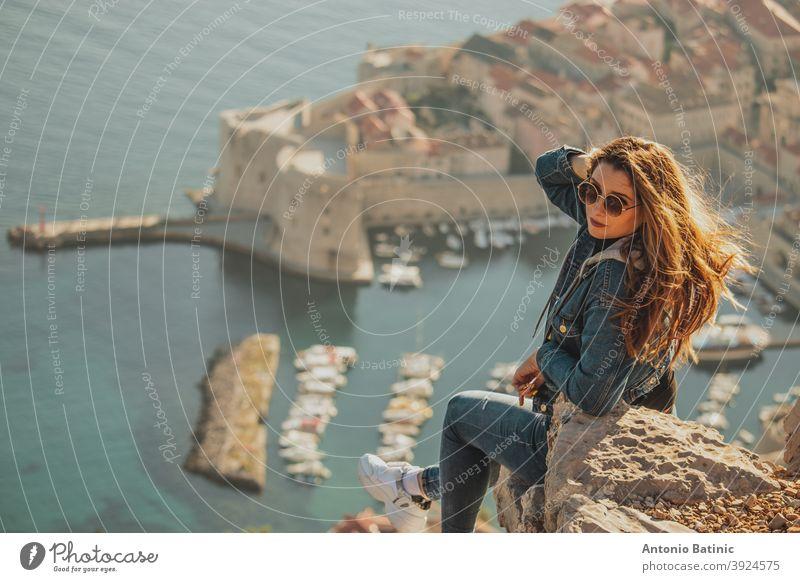 Attraktive Brünette von hinten gesehen posiert, während sie auf einem Stein über der Stadt Dubrovnik sitzt, Umrisse der majestätischen Altstadt im Hintergrund. Reisende besuchen die Mauern und den Berg Srd