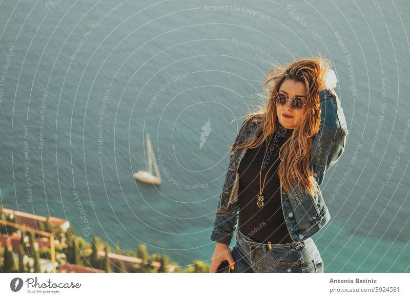 Porträt einer attraktiven Brünette mit Sonnenbrille posiert sinnlich mit dem hellblauen adriatischen Meer hinter ihr. Kleines Segelboot auf dem Meer in der Nähe von Dubrovnik, Konzepte der Reise mit copyspace Raum