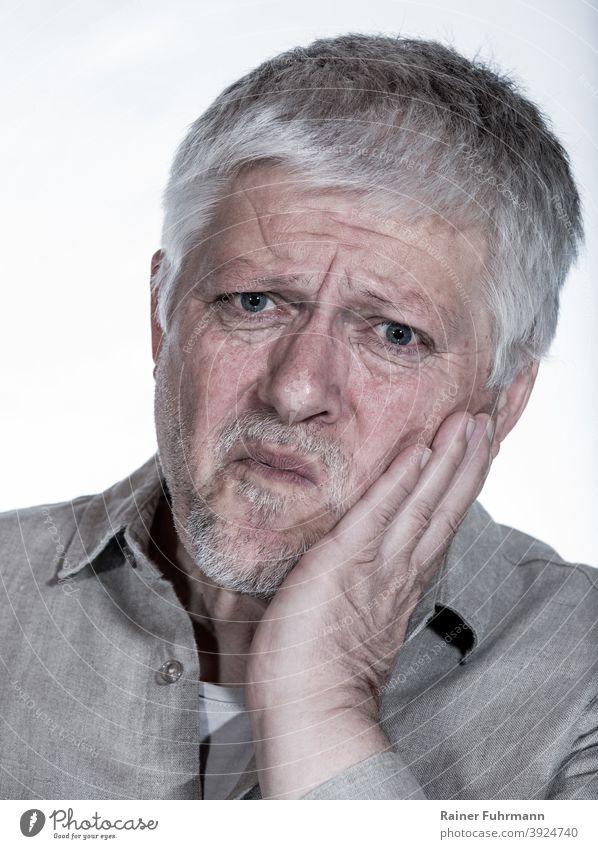 Ein älterer Mann hält sich die Wange. Er hat Zahnschmerzen. Porträt Freisteller Hand Zähne Gesundheitswesen Mensch Zahnarzt Mund Zahnmedizin dental Medizin