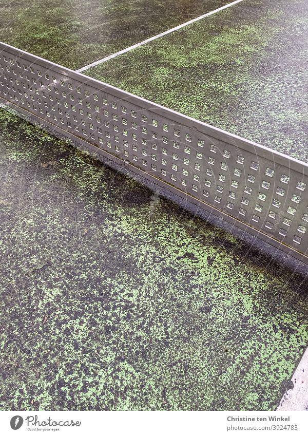 Alte und abgenutzte grau grüne Tischtennisplatte aus Beton im Freien mit 'Netz' aus festem Kunststoffgitter Tischtennisnetz alt Abtrennung Freizeit & Hobby