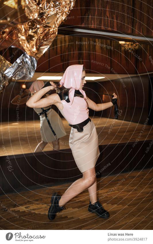 Ein Modeshooting für eine Latexbekleidungsmarke mit einem schönen, in Rosa gekleideten Model. Die Retro-Vintage-Holz-Hintergrund ist eine schöne Übereinstimmung für diese.