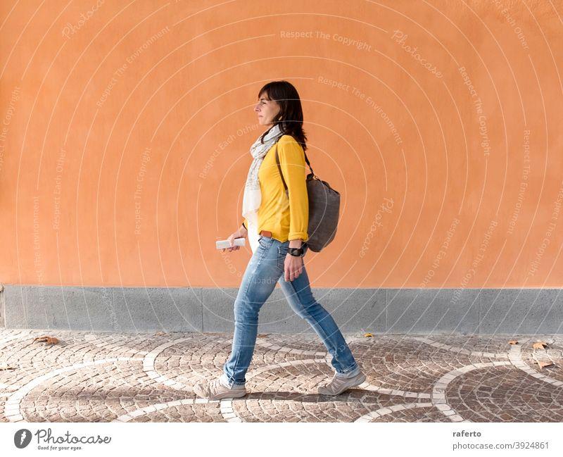 Seitenansicht eines Backpacker-Reisenden zu Fuß gegen orange Wand in der Stadt Frau laufen Rucksack Straße im Freien Großstadt Person urban 1 Reisender Urlauber