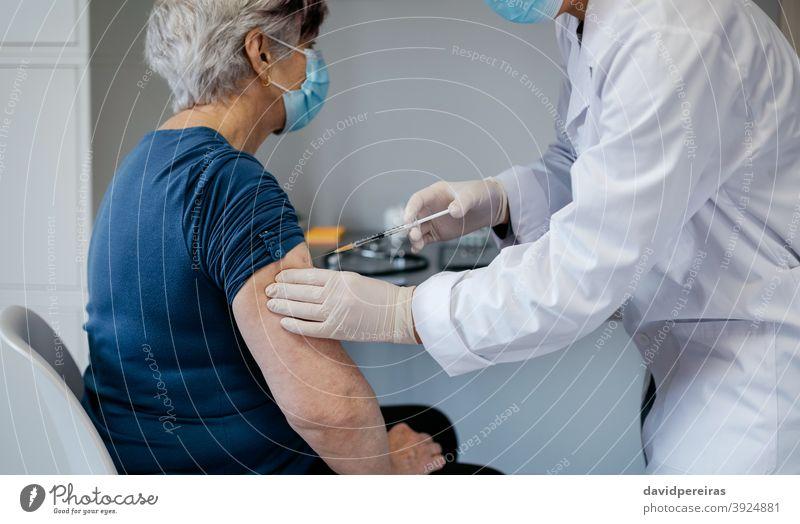 Seniorin wird gegen Coronavirus geimpft Impfstoff covid-19 geduldig älter einspritzend Impfung Arzt Spritze Medizin Einspritzung Gesundheit medizinisch