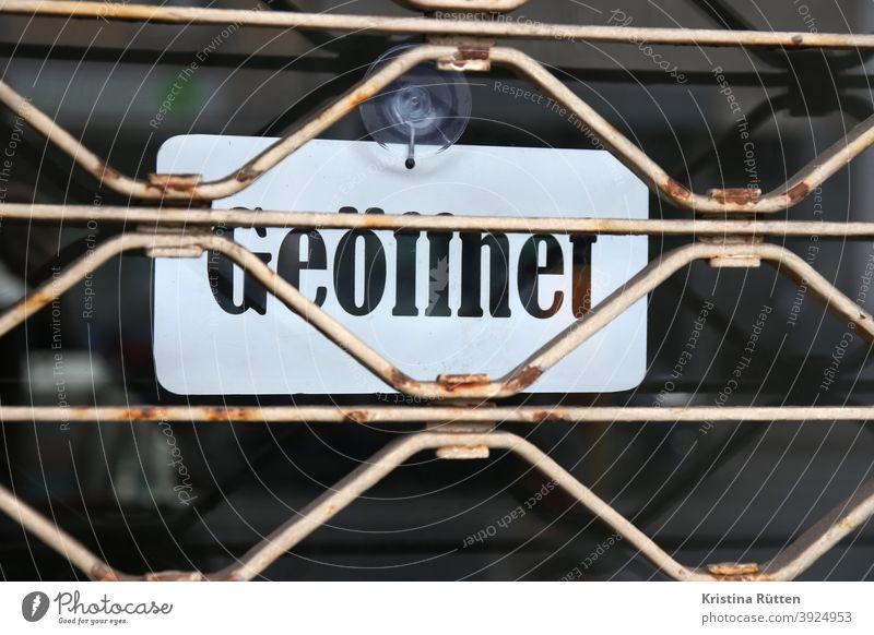 geöffnet schild hinter geschlossenem rollgitter aushang verschlossen zu widersprüchlich widerspruch tür eingang öffnungszeiten geschäftszeiten business laden