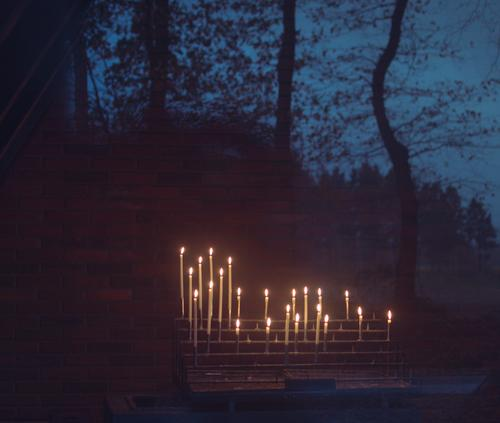 Kerzenaltar mit brennenden Kerzen in einer Kapelle, durch eine Glastür fotografiert. Es spiegeln sich Bäume und der Abendhimmel zur blauen Stunde Opferkerzen