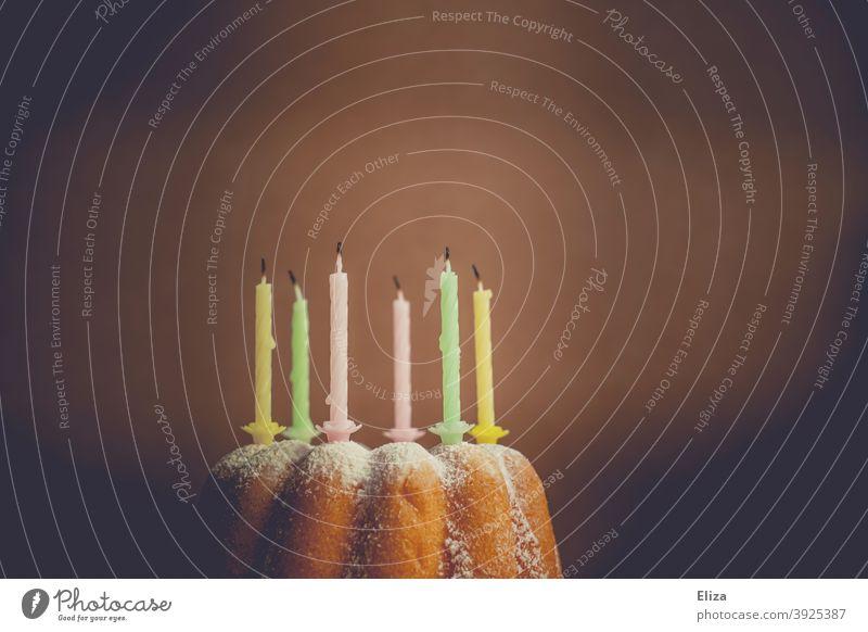 Gugelhupf mit ausgeblasenen Geburtstagskerzen Kuchen Guglhupf Geburtstagskuchen Kerzen bunt Geburtstagsfeier vorbei Kindergeburtstag Backwaren