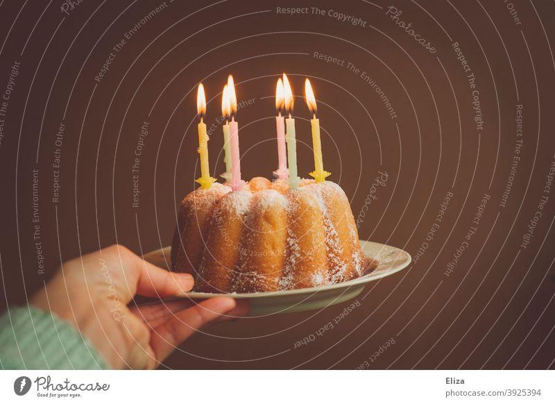 Hand hält einen Geburtstagskuchen mit brennenden Kerzen Geburtstagskerzen Kuchen happy Birthday Geburtstagsfeier Guglhupf Feste & Feiern Kindergeburtstag