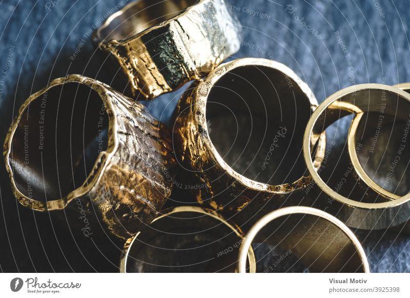 Nahaufnahme von mehreren goldenen Ringen, die auf einer Schiefertafel gestapelt sind abstrakt Detailaufnahme Mode schick glänzend Design metallisch dekorativ