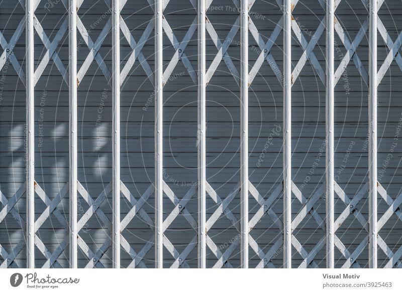 Weiße Sicherheitsgitter an einem städtischen Fenster mit einem geschlossenen Rollladen Hintergrund abstrakt Fensterladen Bars Detailaufnahme Architektur urban