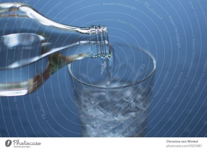 Neustart 2021. Gute Vorsätze, Gesundheit, Diät, Mäßigung, Verzicht. Wasser als Symbol des Lebens. Mineralwasser wird in ein Glas gegossen. Trinkwasser