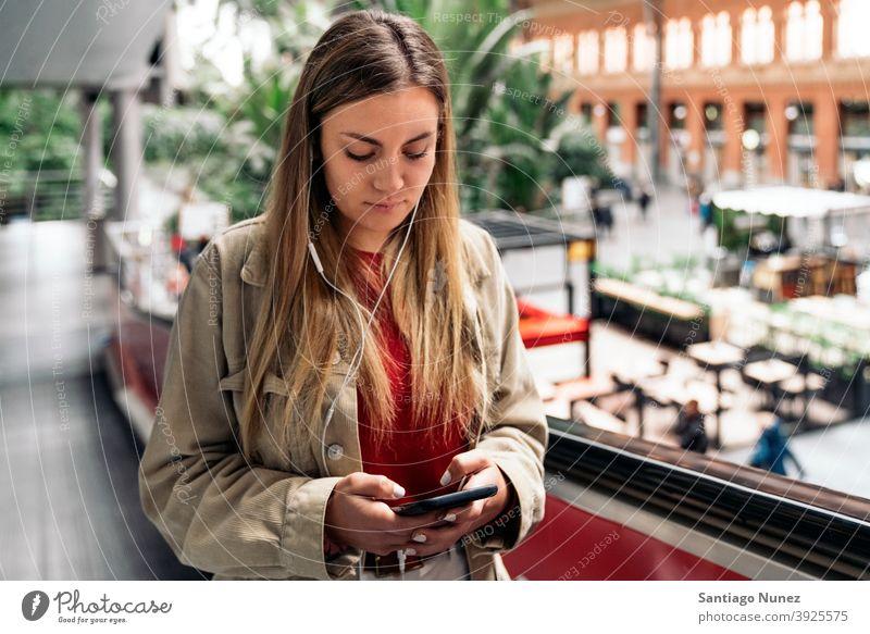Junges Mädchen mit Kopfhörer Porträt jung 20s Vorderansicht blond hübsch Telefon per Telefon Funktelefon Kaukasier Blick Stehen Frau Smartphone hören benutzend