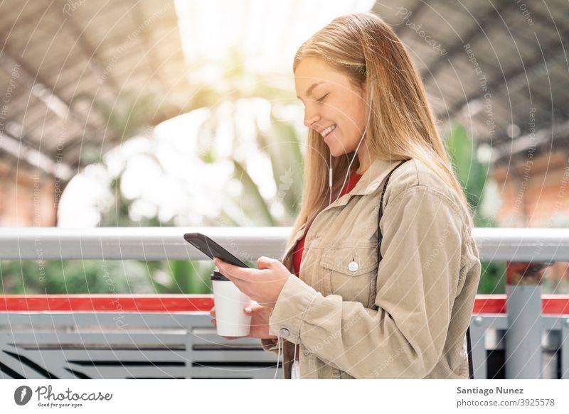 Smiley Mädchen Blick auf Telefon Seitenansicht Blick auf das Telefon Tasse Kaffee Kopfhörer Porträt jung 20s blond hübsch per Telefon Funktelefon Kaukasier
