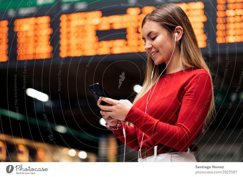 Mädchen im Bahnhof Station Seitenansicht Blick auf das Telefon Kopfhörer Porträt jung 20s blond hübsch per Telefon Funktelefon Kaukasier Stehen Frau Smartphone