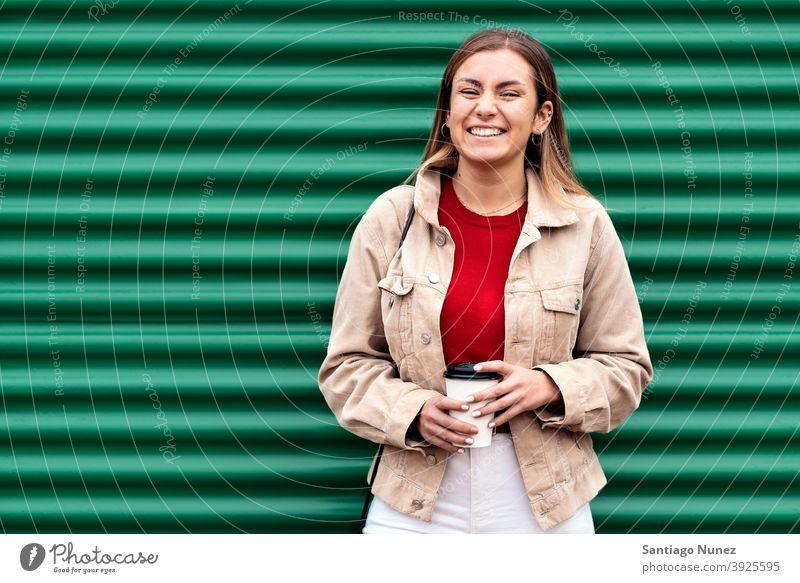 Glückliches junges Mädchen Porträt in die Kamera schauen Tasse Kaffee grüner Hintergrund Stehen hübsch Frau außerhalb im Freien Vorderansicht posierend