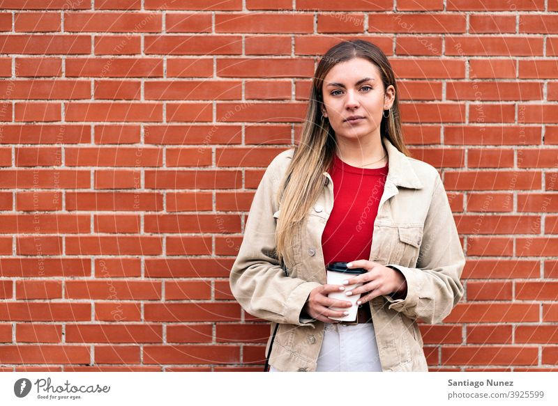 Junges Mädchen Porträt in die Kamera schauen Tasse Kaffee Wand Stehen hübsch Frau jung außerhalb im Freien Vorderansicht posierend eine Person allein