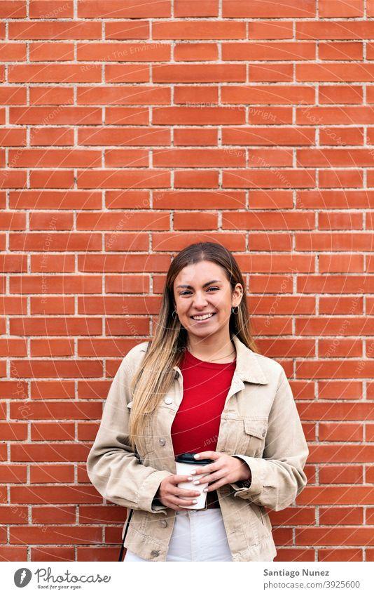 Junges Mädchen lächelnd Porträt in die Kamera schauen Tasse Kaffee Wand Stehen hübsch Frau jung außerhalb im Freien Vorderansicht posierend eine Person allein