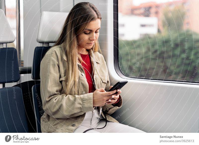 Blondes Mädchen im Zug reisend Kopfhörer Porträt jung 20s Vorderansicht blond hübsch Telefon per Telefon Funktelefon Kaukasier Blick Stehen Frau Smartphone