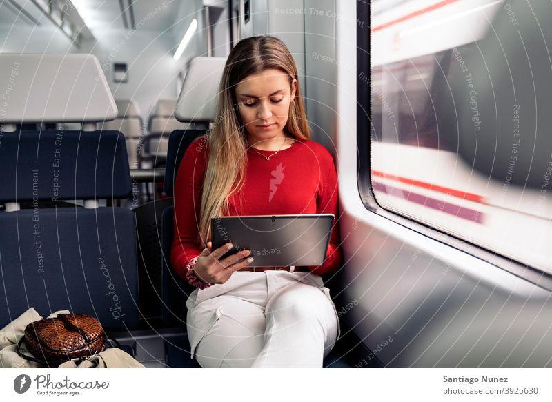 Blondes Mädchen im Zug Tablette reisend Porträt jung 20s Vorderansicht blond hübsch Tablette verwenden Kaukasier Blick Stehen Frau Smartphone Reisender Verkehr