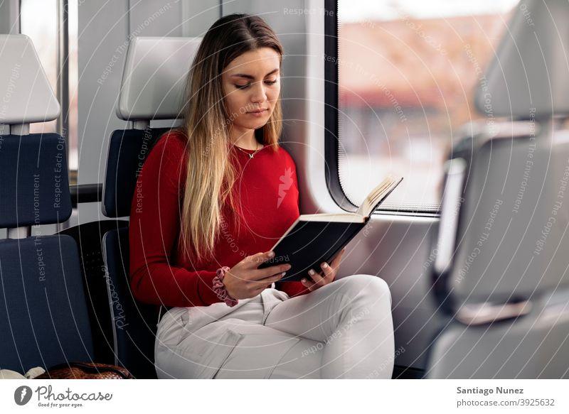 Mädchen liest Buch im Zug lesen fokussiert reisend Porträt jung 20s Vorderansicht blond hübsch Kaukasier Blick Frau Reisender Verkehr im Innenbereich