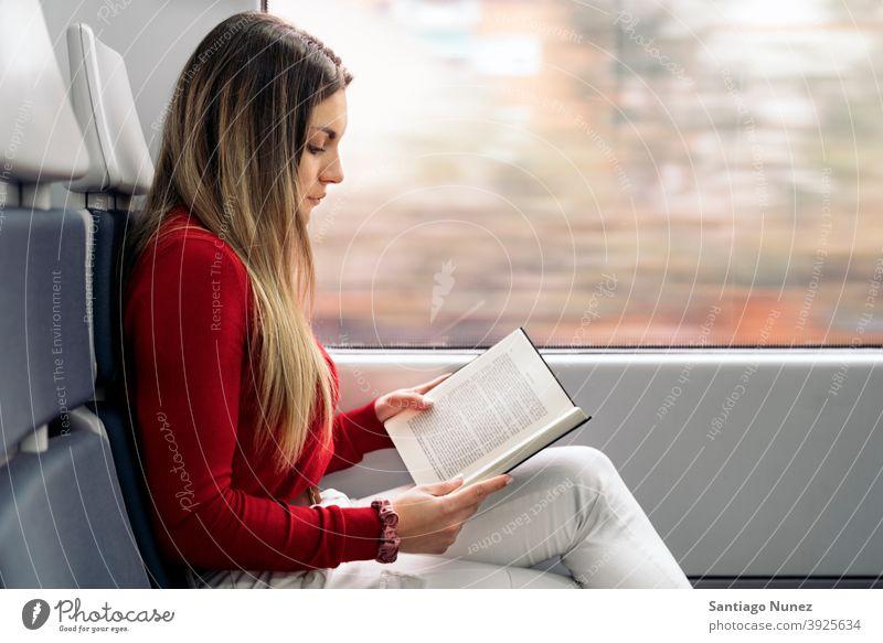 Mädchen liest Buch im Zug Seitenansicht lesen fokussiert reisend Porträt jung 20s blond hübsch Kaukasier Blick Frau Reisender Verkehr im Innenbereich