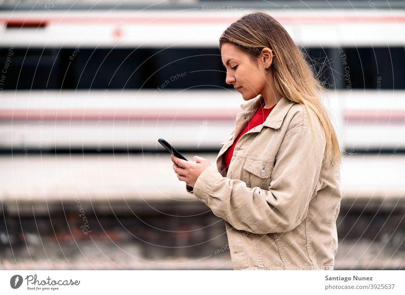 Blondes Mädchen wartet auf den Zug Seitenansicht Frau Kaukasier Bewegung Porträt per Telefon Tippen Blick Hintergrund Stehen außerhalb im Freien U-Bahn Verkehr