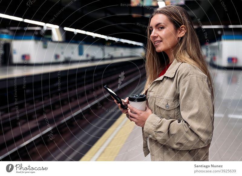 Junges Mädchen wartet auf dem Bahnsteig Seitenansicht Frau Kaukasier Porträt per Telefon Tippen Blick Hintergrund Stehen im Innenbereich im Freien U-Bahn