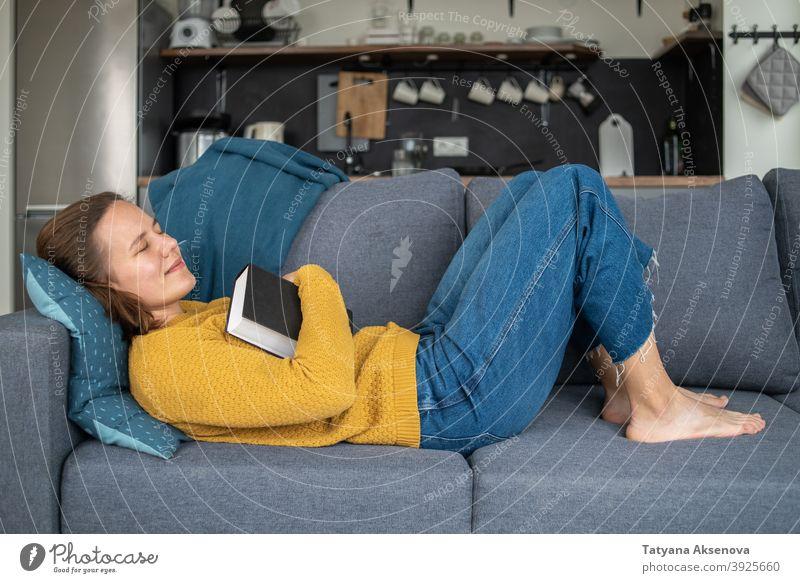 Frau schläft nach dem Lesen lesen schlafen Buch im Innenbereich Sofa heimwärts Erholung Wohnzimmer bequem Person Lifestyle Kaukasier Erwachsener Freizeit Liege