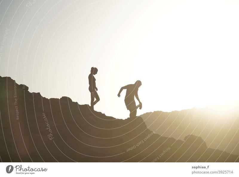 Silhouette von Paar zu Fuß bergab im Gegenlicht bei Sonnenuntergang Berge u. Gebirge Urlaub laufen Abenteuer Hintergrundbeleuchtung wandern Hügel Spaziergang