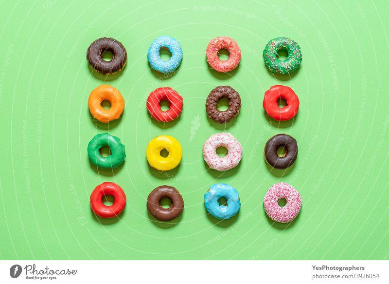 Schokoladen-Donuts in der Draufsicht. Mehrfarbig glasierte Krapfen obere Ansicht ausgerichtet sortiert Hintergrund gebacken Bäckerei blau Frühstück Kuchen