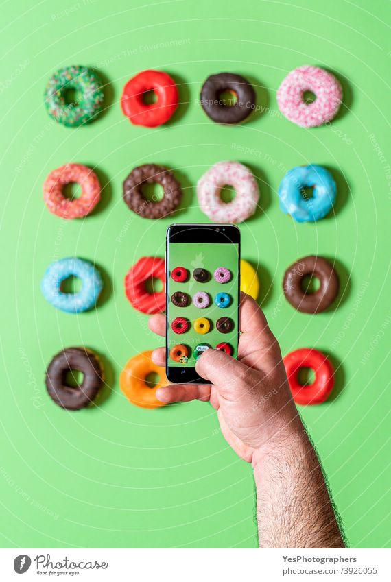 Aufnehmen von Fotos von Donuts mit dem Smartphone. Fotografieren von Lebensmitteln in der Draufsicht. obere Ansicht ausgerichtet sortiert Hintergrund gebacken