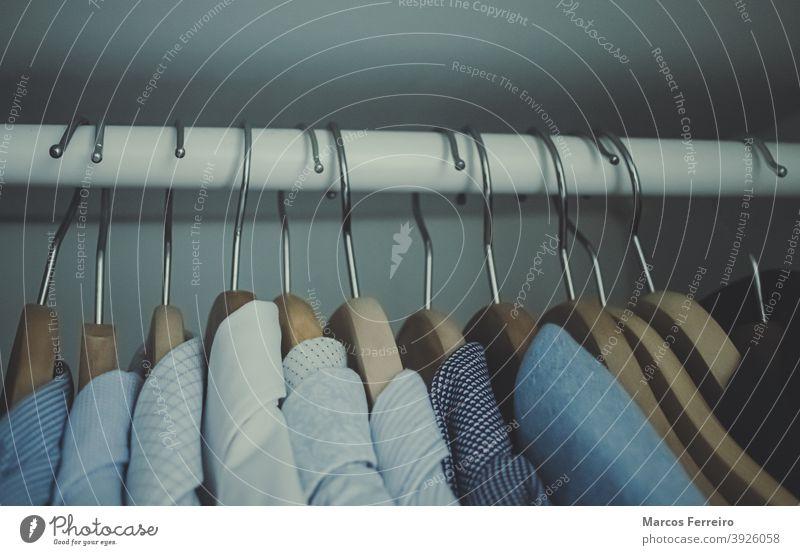 Kleiderbügel mit Kleidung in einem Kleiderschrank stylisch hängen erhängen Stilrichtung Mode Ablage anhaben farbenfroh Bekleidung Hemd Einzelhandel Frau Gewebe