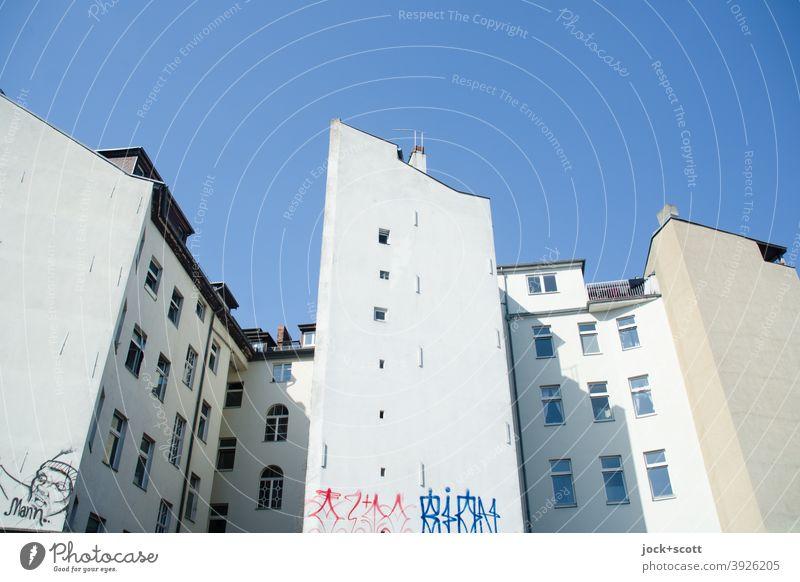 Öffnungen in außenliegender Brandwand Stadthaus Brandmauer Wolkenloser Himmel Fassade Hinterhof Symmetrie authentisch Architektur Graffiti Straßenkunst