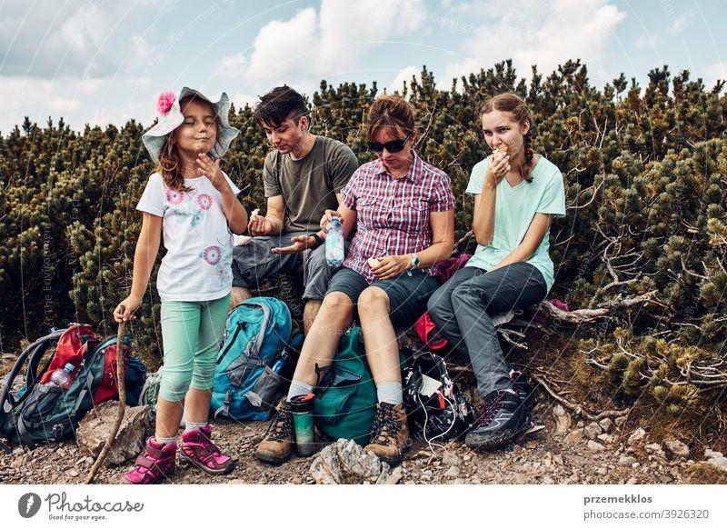 Familie mit Pause und Essen Snacks während der Reise in den Bergen. Familie aktiv verbringen Sommerurlaub zusammen Aktivität Abenteuer Frau Freiheit Spaß grün