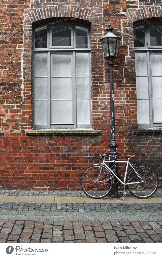 Weißes Fahrrad an eine Straßenlaterne vor einer Backsteinmauer gebunden Hintergrund retro Wand altehrwürdig Architektur Baustein Europa Europäer Fassade