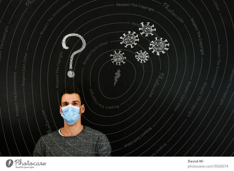 Coronavirus - Mann denkt über Corona nach coronavirus mutation denken Gedanken ? Fragezeichen Virus Zukunft Angst Zukunftsangst pandemie Mundschutz