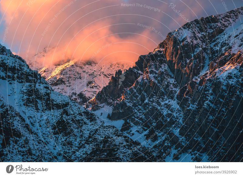 Sonnenuntergang in felsigen Bergen mit sonnenbeschienenen Wolken der österreichischen Alpen in Mieming, Tirol, Österreich Winter Berge u. Gebirge Schnee Cloud